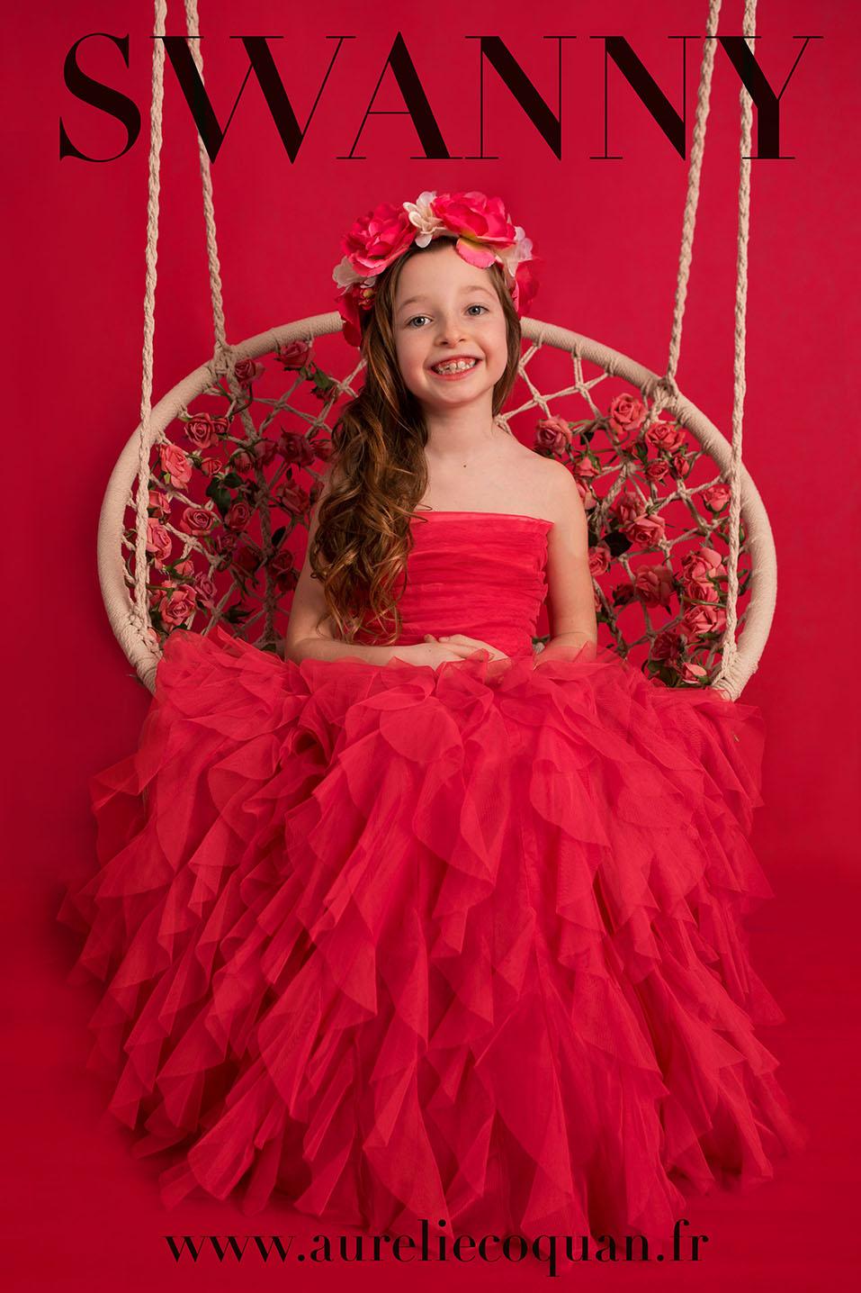 Anniversaire de princesse : en robe de princesse rouge sur une balançoire par Aurélie Coquan Photographe